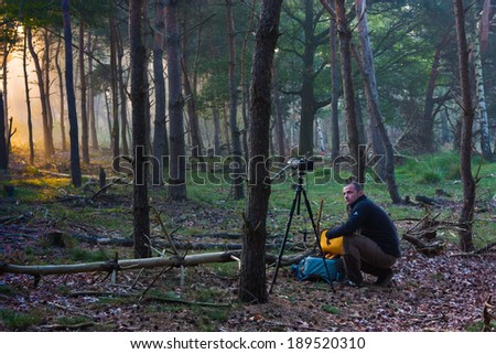 Photographer preparing to take some pictures in the woods - stock photo