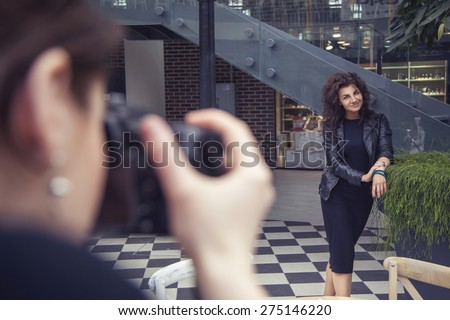 Photographer shooting a beautiful brunette woman on a walk on european city street in daylight. outdoors - stock photo