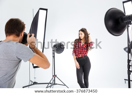 Photographer shooting model in professional studio with softboxes - stock photo