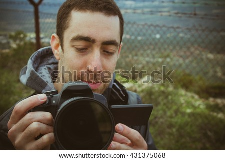 Photographer shooting outside with digital camera. - stock photo