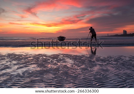 Photographer shooting the Boats at the beach during sunset - stock photo