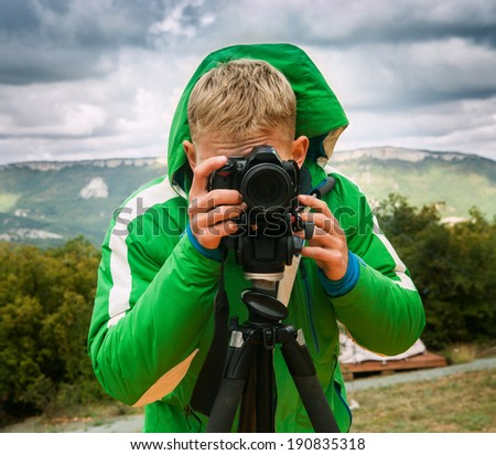 Photographer shoots with DSLR Camera using tripod - stock photo