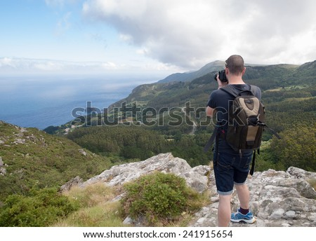 Photographer sightseeing and photographing a beautiful coastal landscape in Galicia, Spain