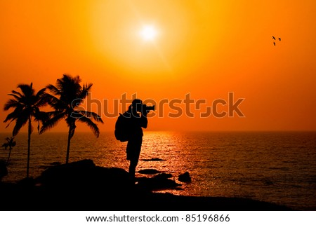 Photographer silhouette shooting sea outdoors on the rock cliff near palm trees at sunset background - stock photo