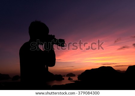 Photographer silhouette shooting seaand landscape  outdoors at sunset sunrise background