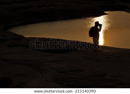 Photographer silhouette sunset at rock holes Stone View Sam Pan Bok Grand Canyon in thailand   - stock photo