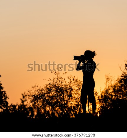 Photographer silhouetted against a golden sunset sky in Africa - stock photo