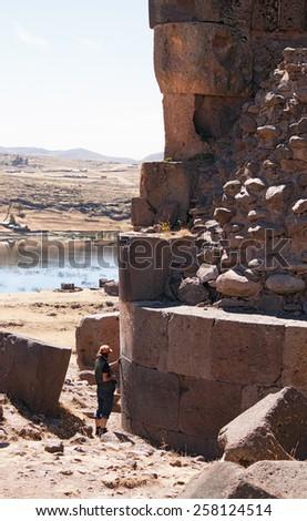 photographer standing near the tower of Sillustani - pre-Incan burial tombs on the Lake Umayo near Puno, Peru - stock photo