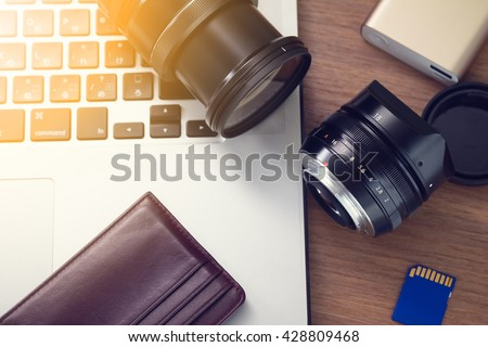 Photographer table , camera lens, sd cards, portable power bank, laptop on table.  - stock photo