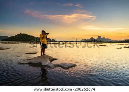Photographer take a picture of beautiful sunset in lake - stock photo