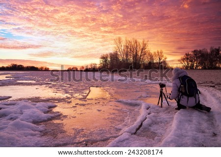 Photographer take pictures on the river bank in winter. Girl, photographed sunset - stock photo