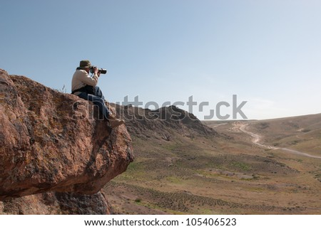 Photographer takes pictures sitting on the big hanging stone