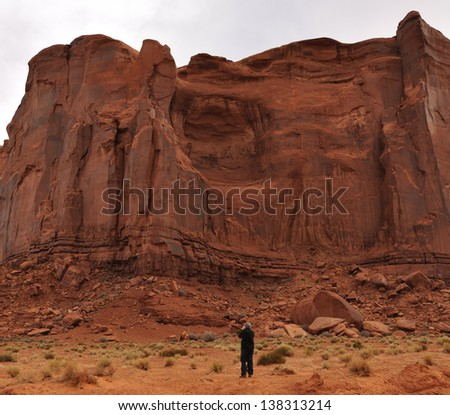 Photographer Taking a Photo of the Rain God Mesa in Monument Valley - stock photo