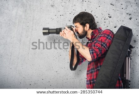 Photographer taking a photo over textured background - stock photo