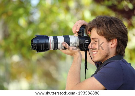 Photographer taking a photograph outdoor with a dslr camera with a green background - stock photo
