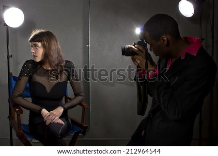 photographer taking an actress photo with flash strobes - stock photo
