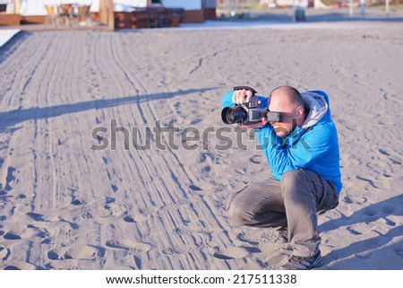 photographer taking photo of models couple on beautiful tropical beach at summer - stock photo