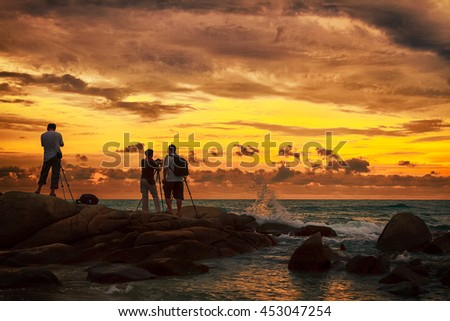 Photographer taking photo on the beach during sunset - stock photo