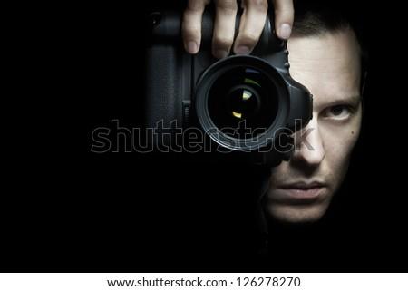 Photographer taking photo with camera on black background - stock photo