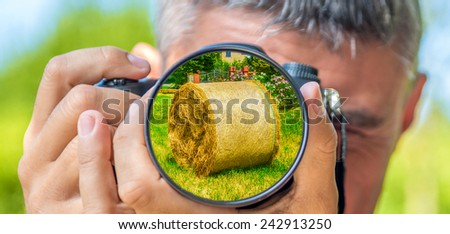 Photographer taking photo with DSLR camera at Hay Bales. Shallow DOF - stock photo