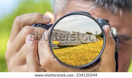 Photographer taking photo with DSLR camera at Solar Panels. Shallow DOF - stock photo