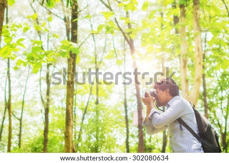 Photographer taking photos in a green forest with Film camera  - stock photo