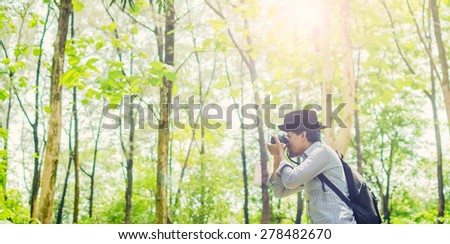 Photographer taking photos in a green forest with Film camera wearing black hat & backpack - stock photo
