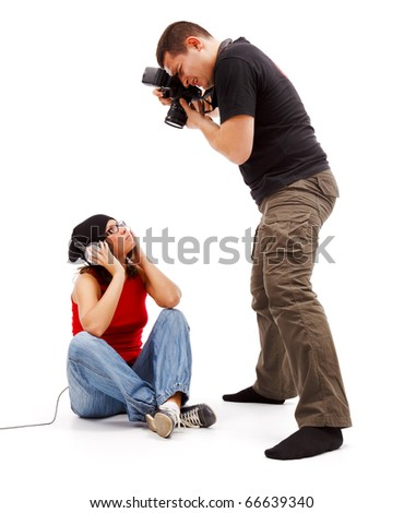 Photographer taking photos of a sitting young model with earphones