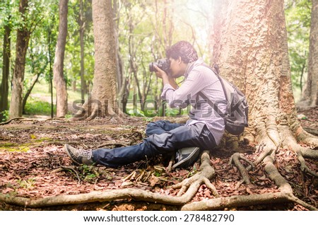 Photographer taking photos sitting under a big tree using digital SLR camera in natural outdoor, vintage look - stock photo