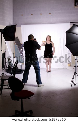 Photographer Taking Pictures of a Model in the Studio - stock photo