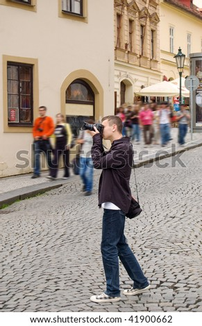 Photographer taking pictures outdoor and tourists passing by - stock photo