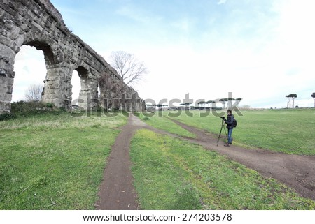 photographer under Roman ruins in a fish-eye view - stock photo