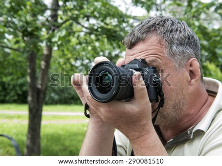 Photographer using a dslr camera - stock photo