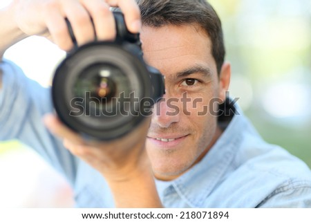 Photographer using reflex camera outside - stock photo