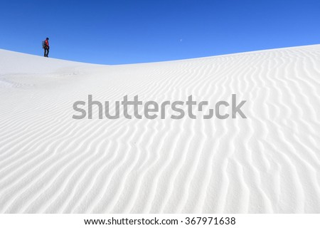Photographer walking on white sand dunes, White Sands National Monument, New Mexico - stock photo