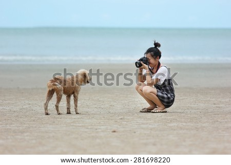 Photographer was taking photos at the beach and she was playing with the dog.