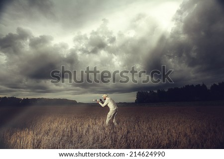photographer with a camera in the bad weather the storm - stock photo