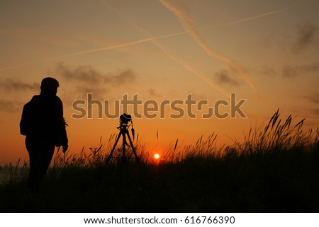 Photographer with a camera on a tripod at sunrise