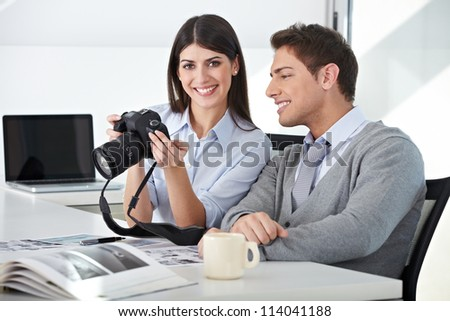 Photographer with assistant holding camera in their office - stock photo