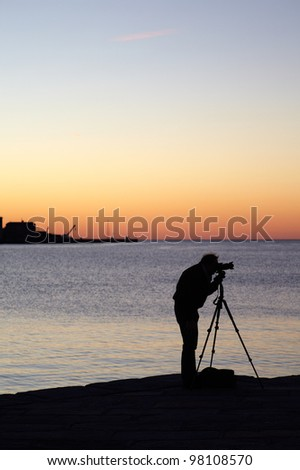 Photographer with camera and tripod take a picture at sunset - stock photo