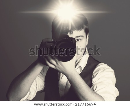 Photographer with camera in the studio - stock photo