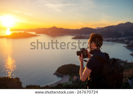 Photographer with professional photo camera and backpack on the top of the mountain on the beautiful sunset. - stock photo