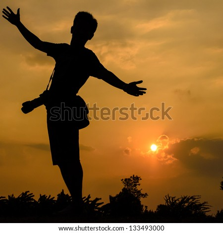 Photographer with sillouette sun and sky - stock photo