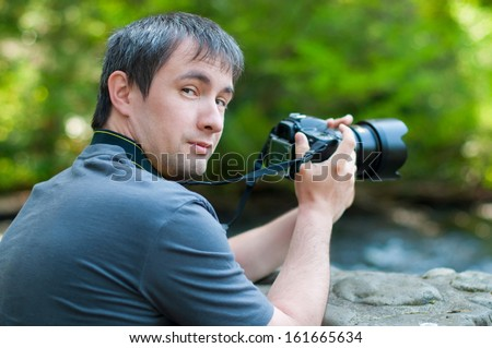 Photographer with the camera turned around and look at the camera - stock photo