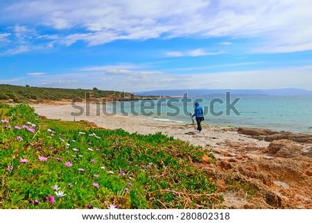 photographer with tripod walking in Le Bombarde beach, Sardinia - stock photo