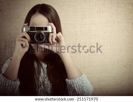 Photographer woman holding retro camera and taking photos, toned - stock photo