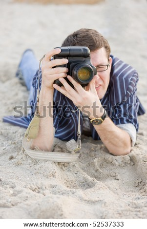 Photographer work with camera on sand - stock photo