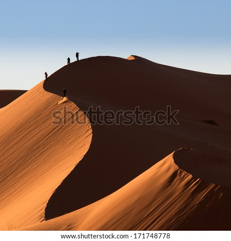 Photographers on dunes of desert Sahara, Morocco - stock photo