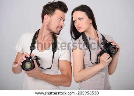 Photographers. Two cheerful photographers holding cameras in their hands and smiling - stock photo