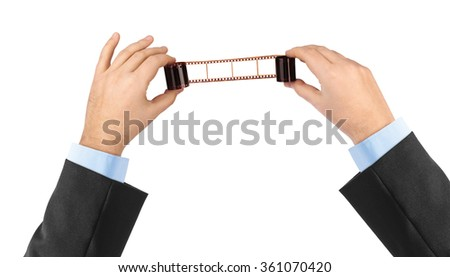 Photographic film in hands isolated on white background - stock photo